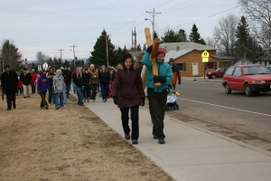 Community members take turns leading the procession, carrying the heavy cross through the streets of Grand Marais.