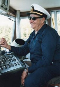 My grandfather, Captain Roy Oberg, at the helm of the Voyageur II.